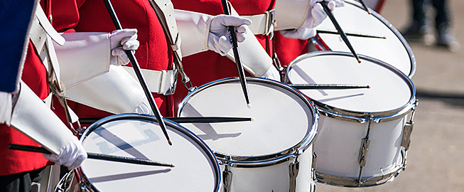 Close up of band in red suits playing snare drums