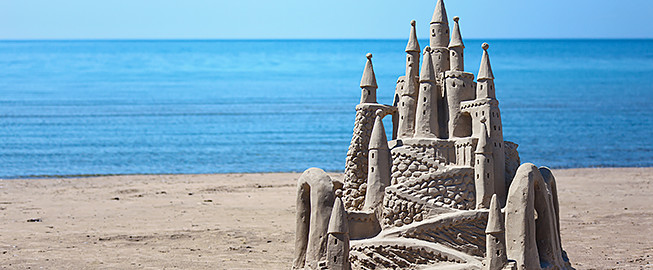 Intricate sand castle with the ocean water in the back