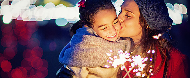 Mom kissing daughter on the cheek while holding sparklers