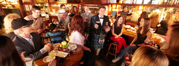 Man in kilt walking through bar filled with people