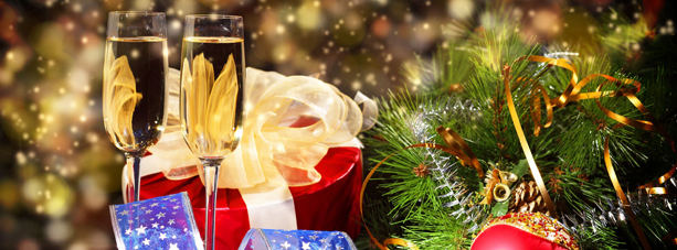 Close up of glasses of champagne next to christmas tree