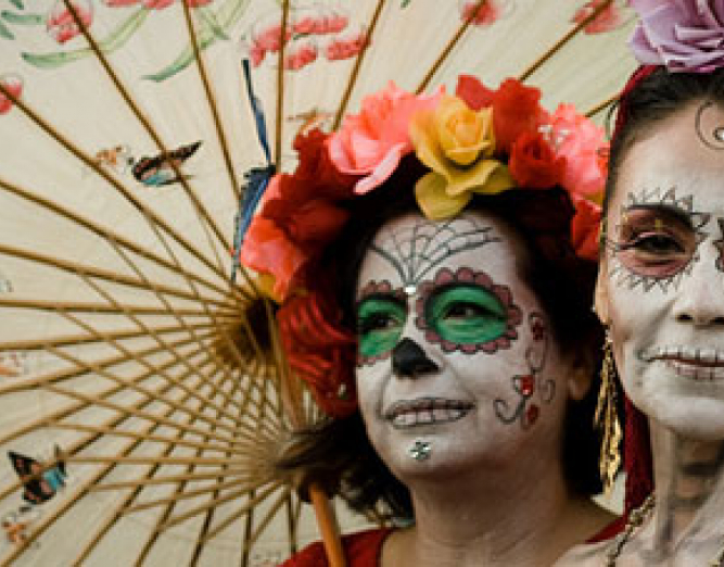 Two women with dia de los muertos face paint