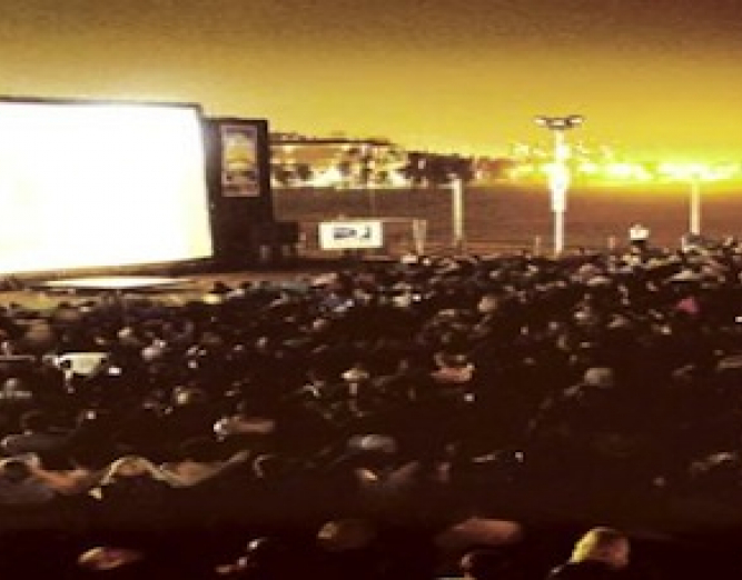 Crowd of people sitting in front of large screen as the sun sets