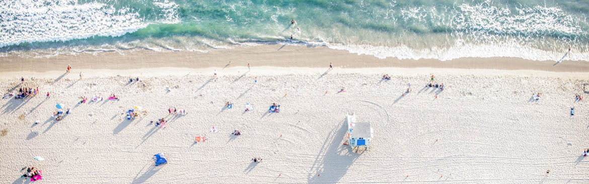 Aerial view of white sand beach with people sun bathing