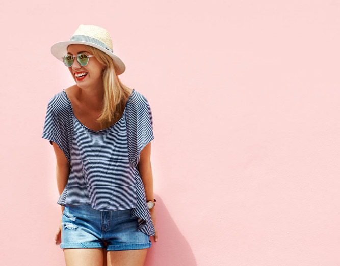 Girl with sunhat leaning against pink wall