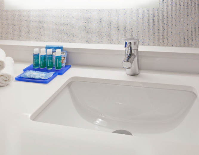White sink with rolled up towels, soap & mouthwash on the side