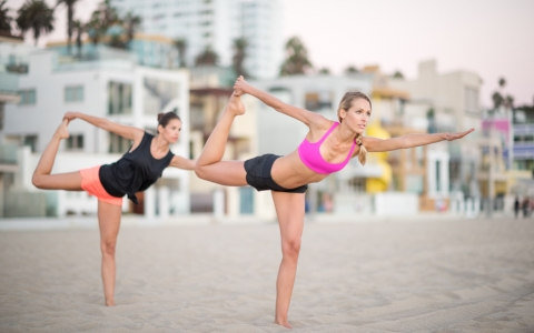 Two women doing yoga pose on beach