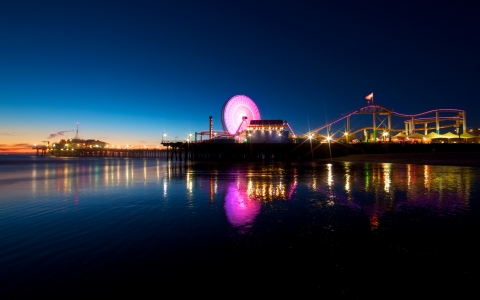 Santa Monica pier lit up at night by the water