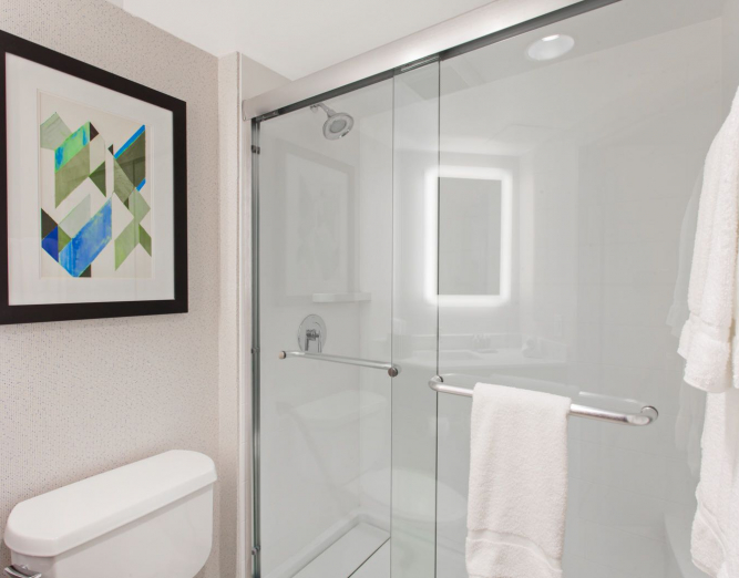 Bathroom with sliding glass shower door & geometric wall art