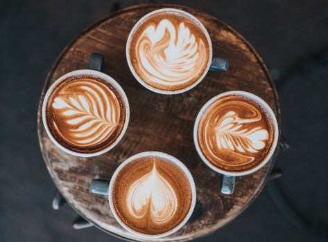 four cups of coffee with latte art
