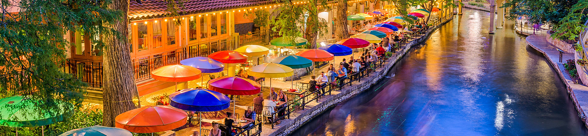 overhead view of the San Antonio riverwalk in the evening with the view of colorful umbrellas