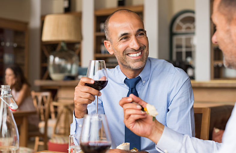 Man smiling at table holding a glass of wine