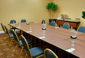 hotel room with one long conference table surrounded with chairs