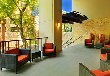 outdoor patio lined with outdoor furniture with orange cushions