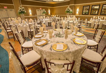 hotel ballroom prepared with round roundtables with white and gold decor