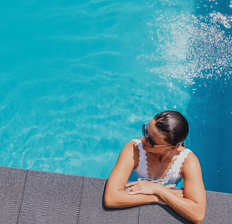 overhead view of a woman leaning on pool deck