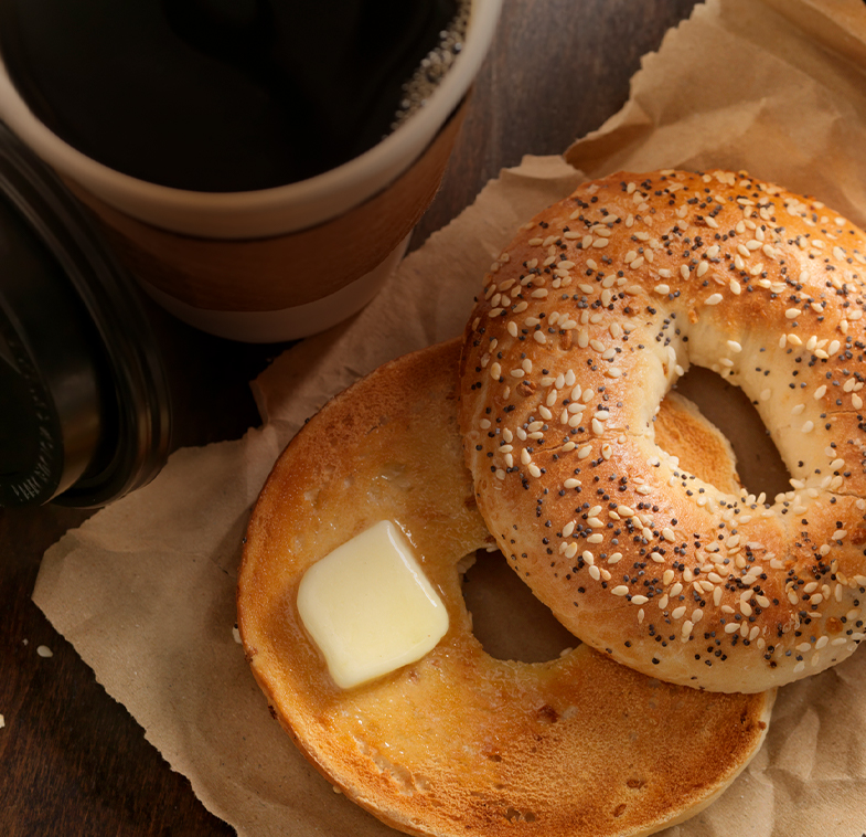 overhead view of bagel with butter and coffee