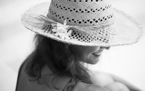 Woman by the pool wearing straw hat