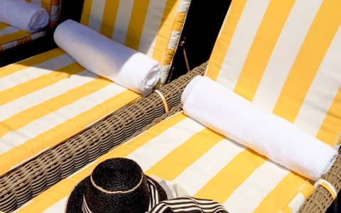Pool loungers with brightly striped cushions & sun hat