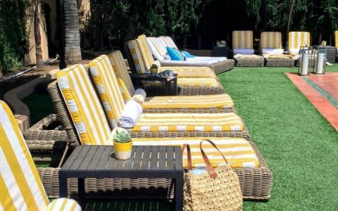 Rows of loungers with brightly stripped cushions on faux grass