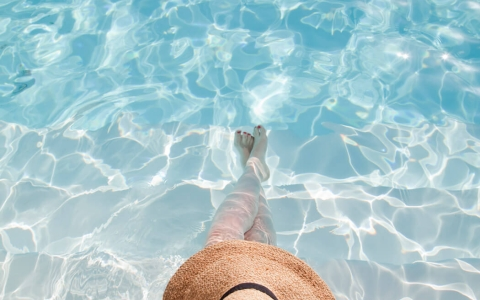 Aerial view of woman with sunhat in the edge of a pool