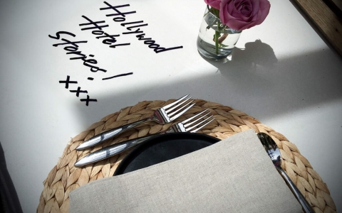 Table set for meal with wicker place mats & Hollywood Hotel Stories written on table