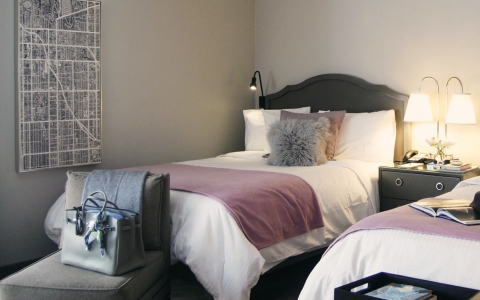 Modern room with two beds, black wooden furniture, cushioned seat at the bedside with purse