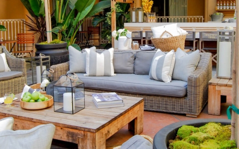 Outdoor seating area with wicker seating with cushions & wooden table