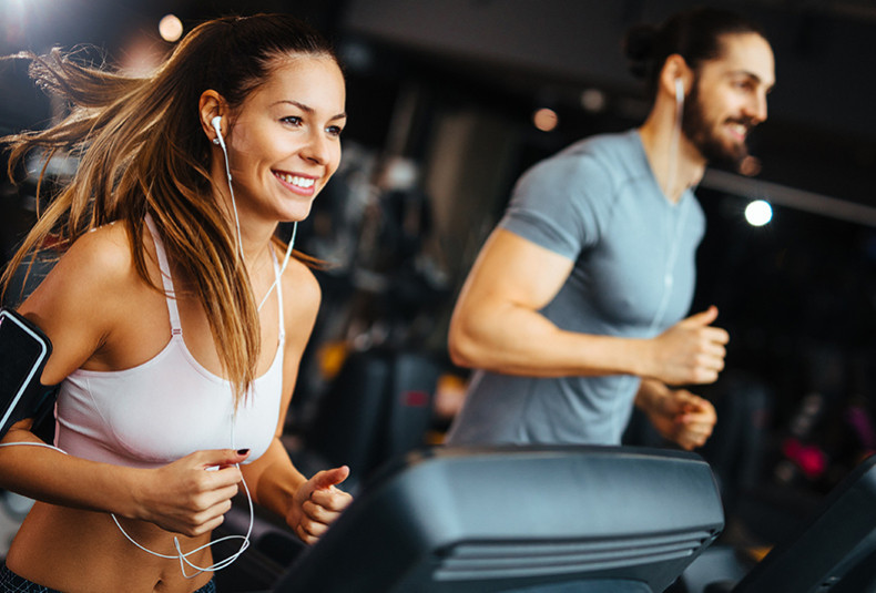 man and woman at the gym running on treadmills