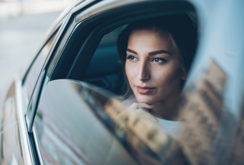 woman in a car looking out a window half rolled down