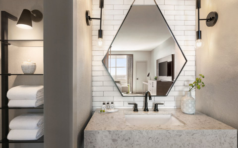 bathroom with a geometric mirror shape, modern lights, vanity, and shelves with towels
