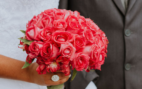close up of a bride holding a bouquet of red flowers with her arms locked with the groom