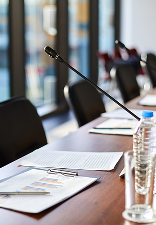 close up of a conference table with documents on the table and microphones at each chair
