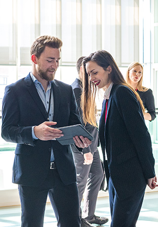 two business people looking at a tablet together at a conference
