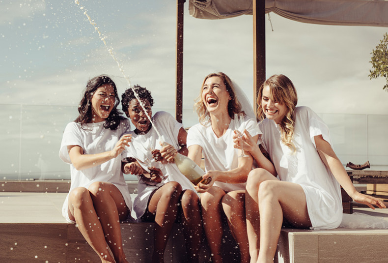 four women wearing white t-shirt dresses popping champagne on a rooftop