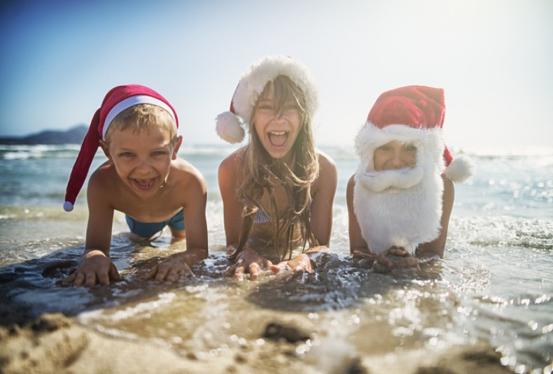 kids at the beach dressed as santa