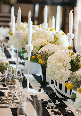 table at a wedding reception decorated with black and white stripes, tall candlesticks, and white flower centerpieces