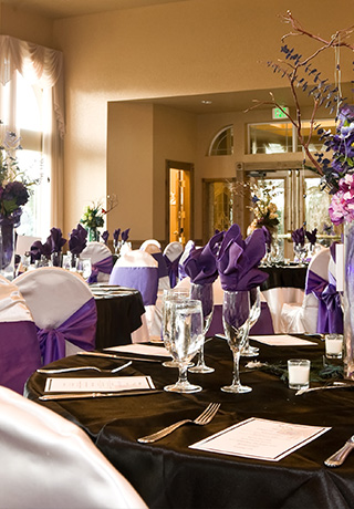 wedding reception tables with white chair covers and purple bows and black tablecloths
