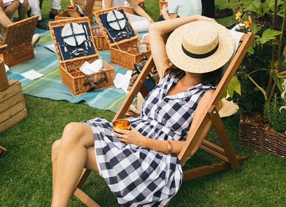 Barefoot Woman with Straw Hat Over Her Face Sits Among Other Picnickers