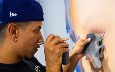 closeup of artist airbrushing a painting