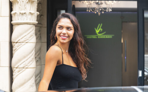 woman smiling in front of hotel entrance