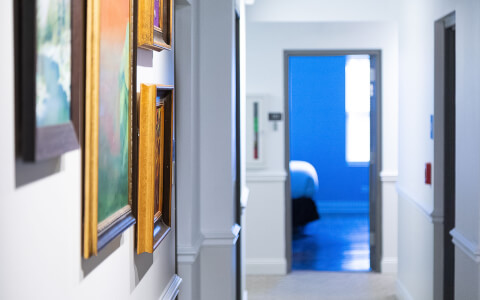 hallway with paintings on the wall looking down to a room lit in blue