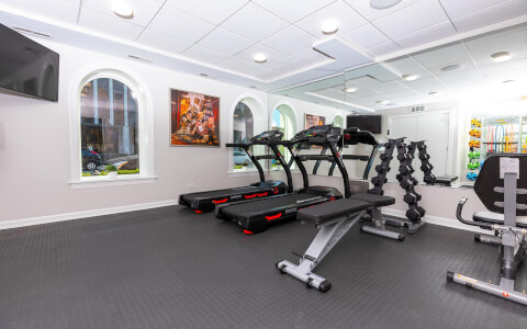 fitness room with two treadmills and weights