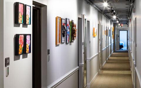 hallway with white walls and lots of colorful paintings