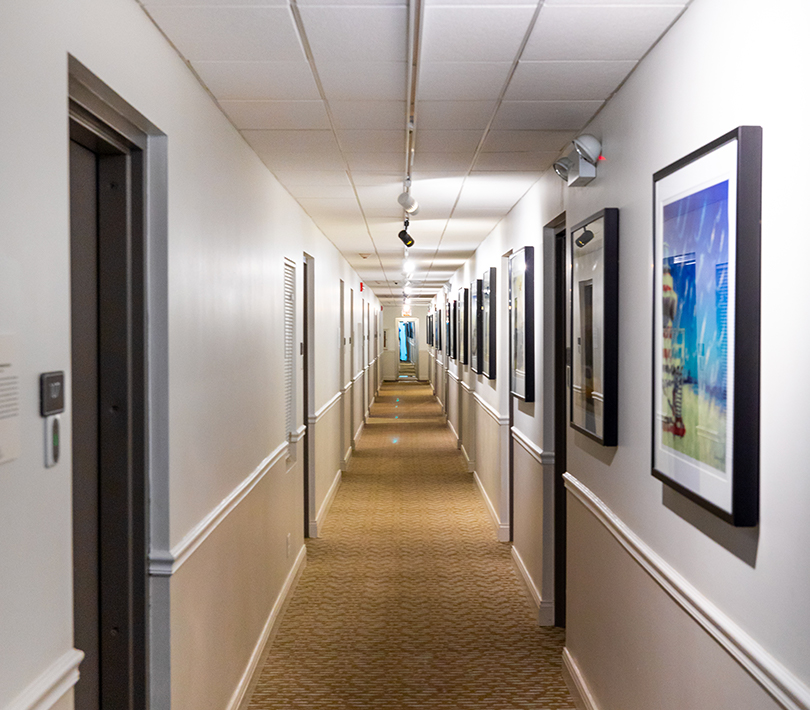 long hallway with paintings all down the right wall