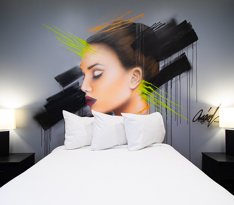 womans head painted on a wall above the guest bed