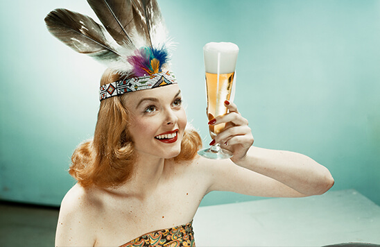 woman wearing an indian headpiece with feathers holding a beer