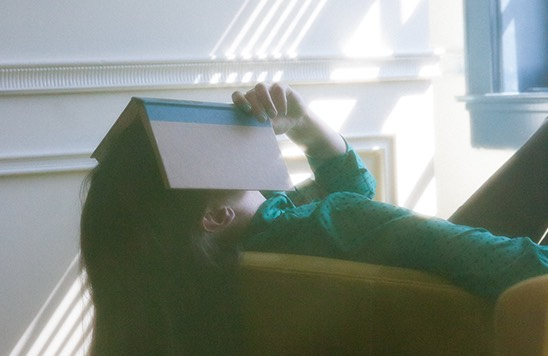 woman hiding her face with a book