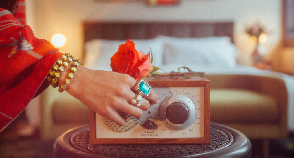 Female hand turning on a radio infront of a hotel bed