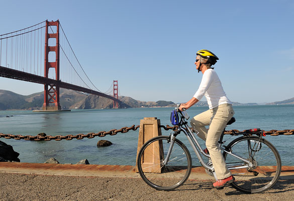 man riding a bike with the golden gate bridge in the back